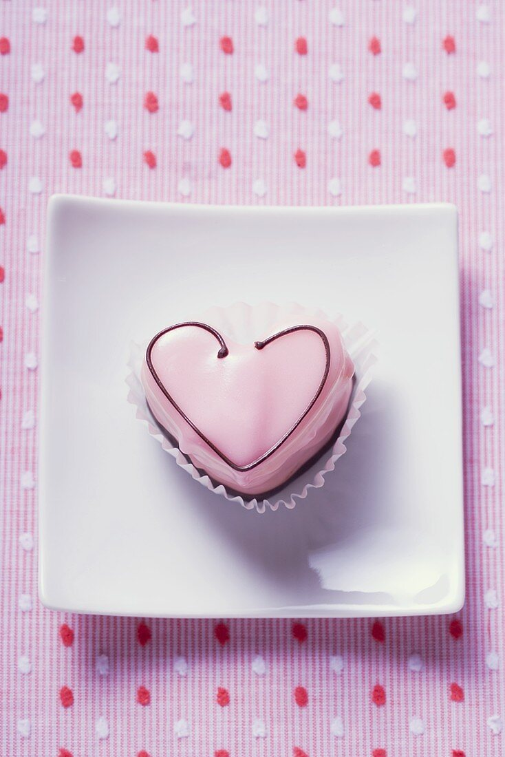 Pink heart-shaped petit four on plate (overhead view)