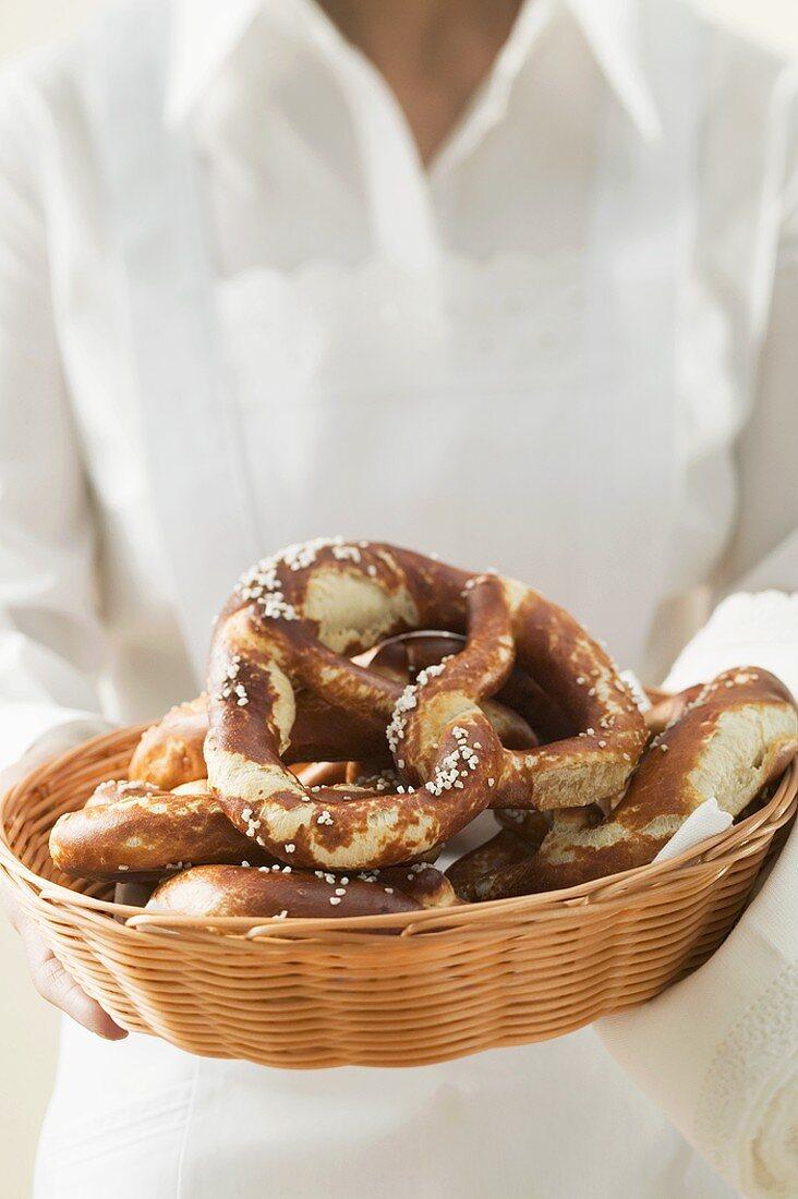 Chambermaid serving soft pretzels in bread basket