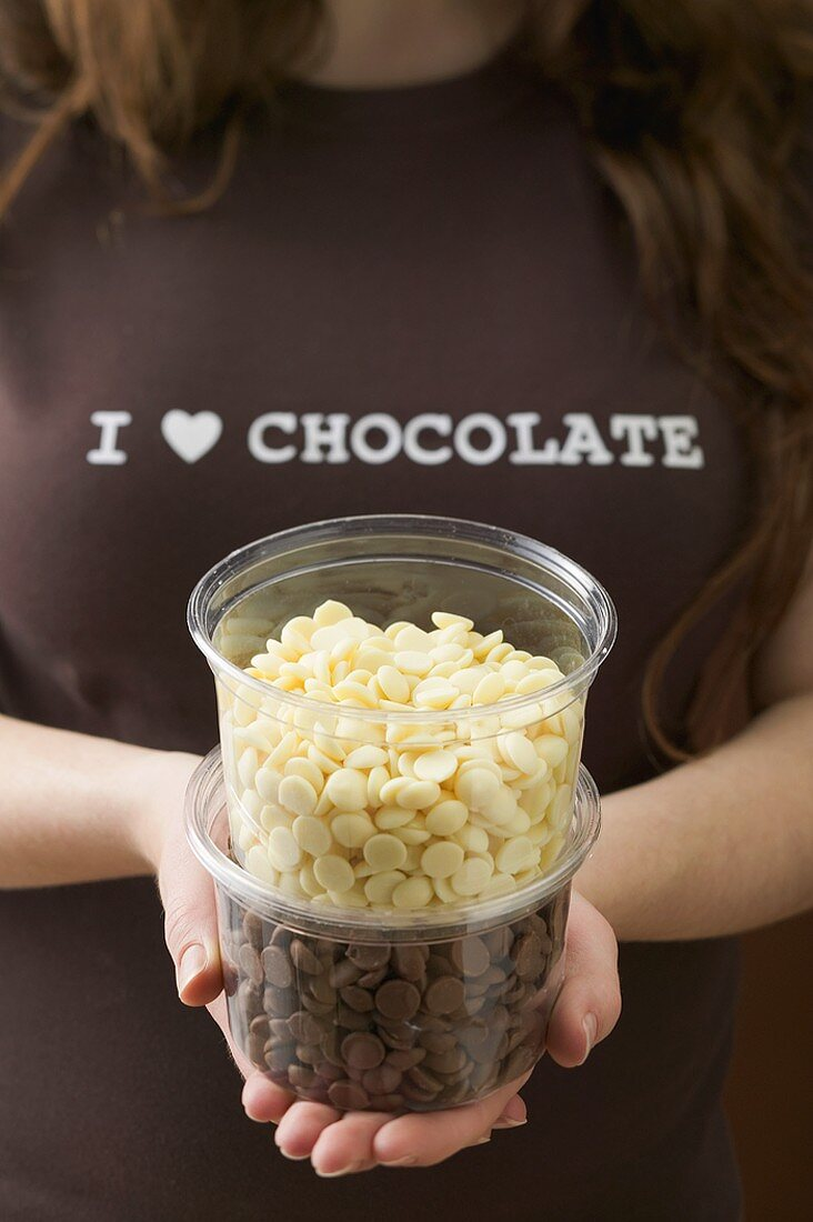 Woman holding two plastic tubs of chocolate chips