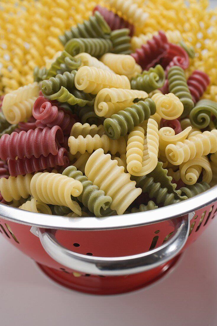 Coloured riccioli in colander, fusilli lunghi in background