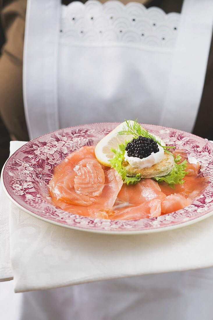 Chambermaid serving smoked salmon with caviar