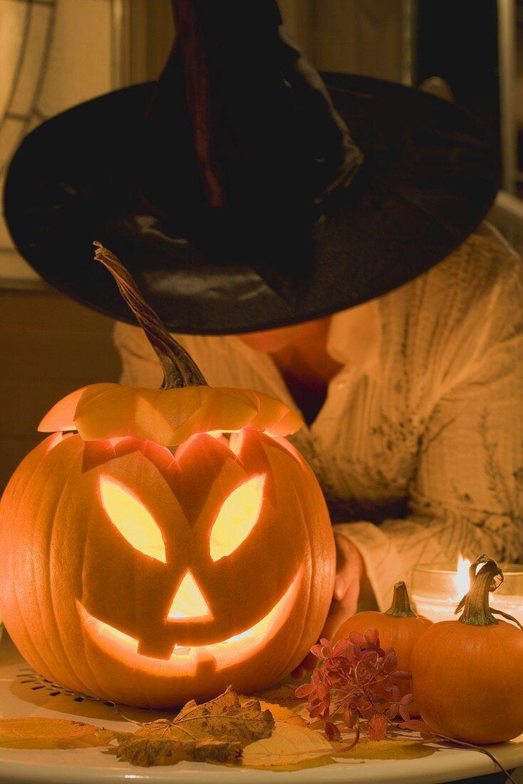 Woman in witch's hat holding pumpkin lantern