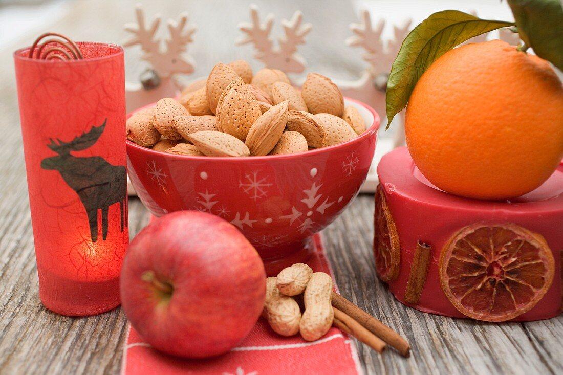 Christmas decoration: nuts, orange, apple, cinnamon, candle