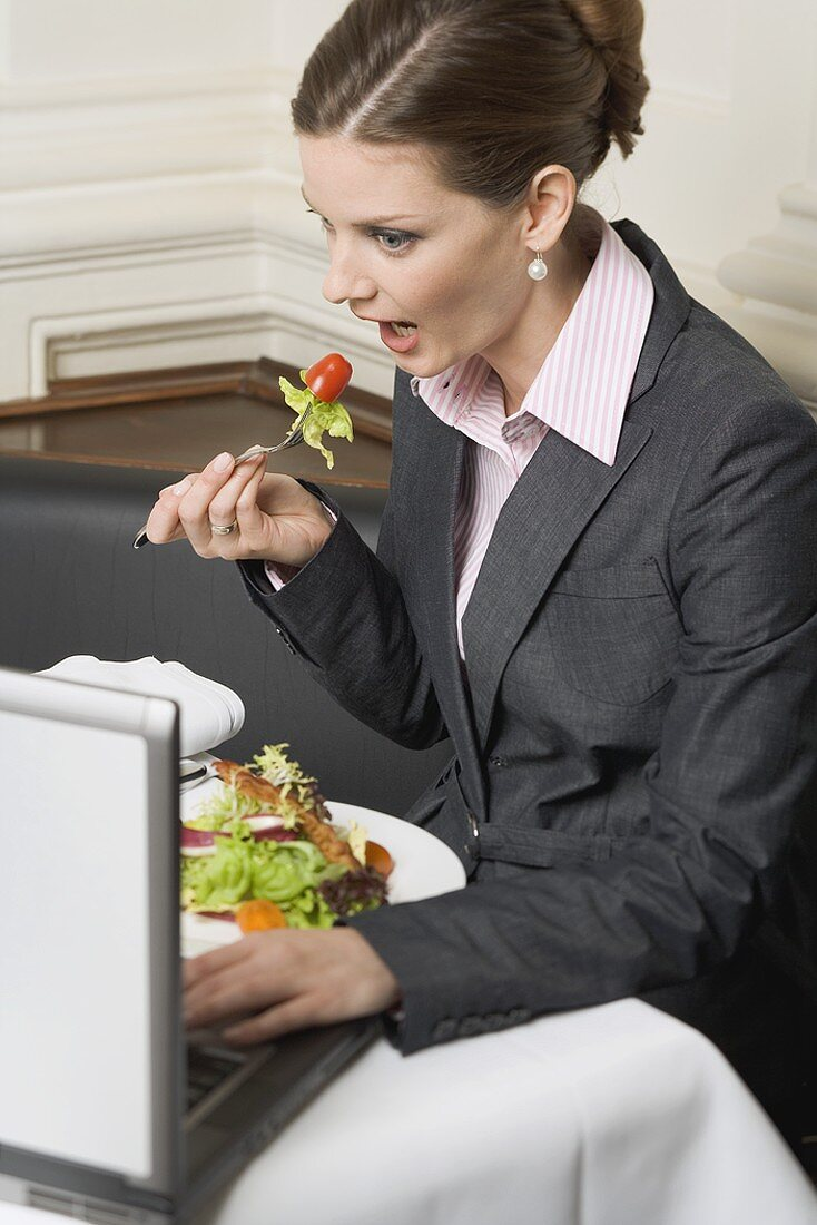 Woman eating salad while working on laptop in restaurant
