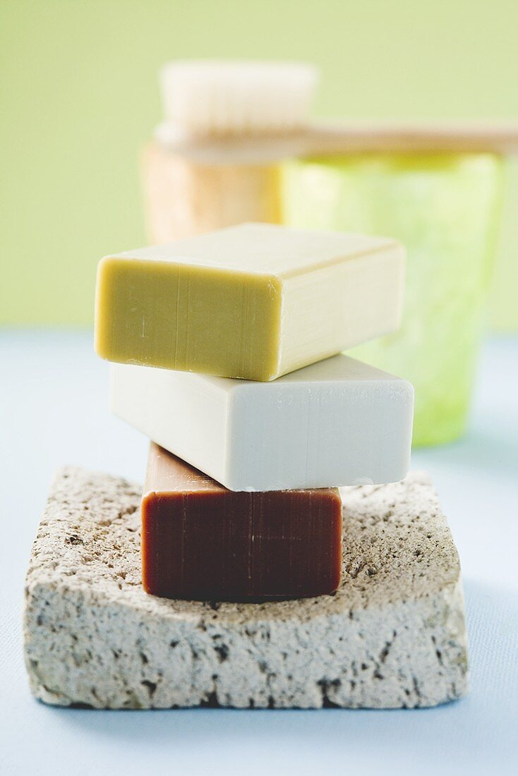 Three bars of soap on pumice stone, windlights, brush