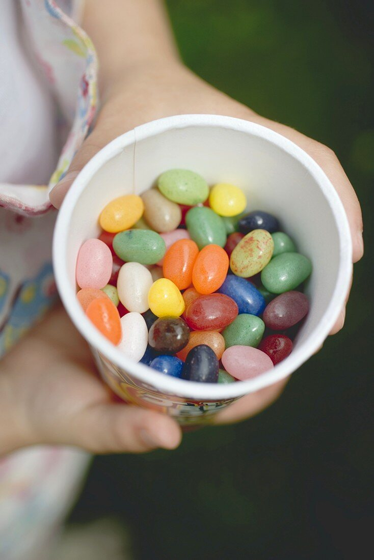 Child's hands holding tub of coloured sugar eggs
