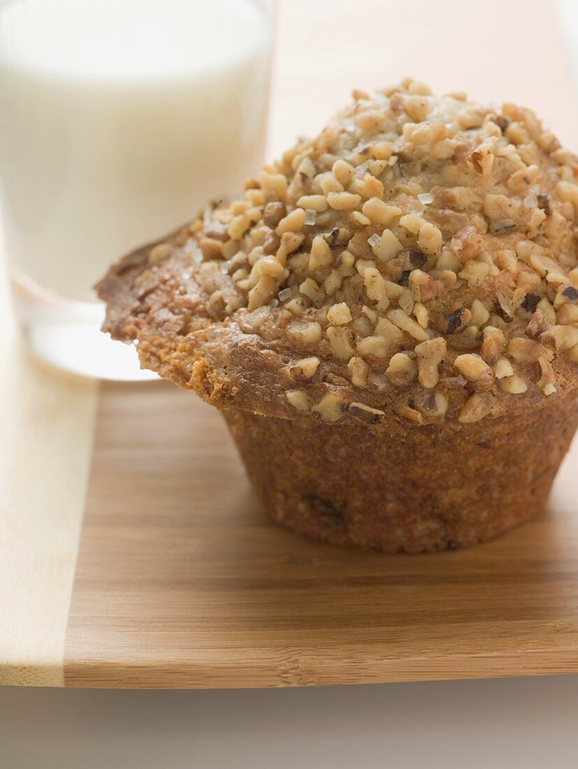 Muffin topped with chopped nuts, glass of milk