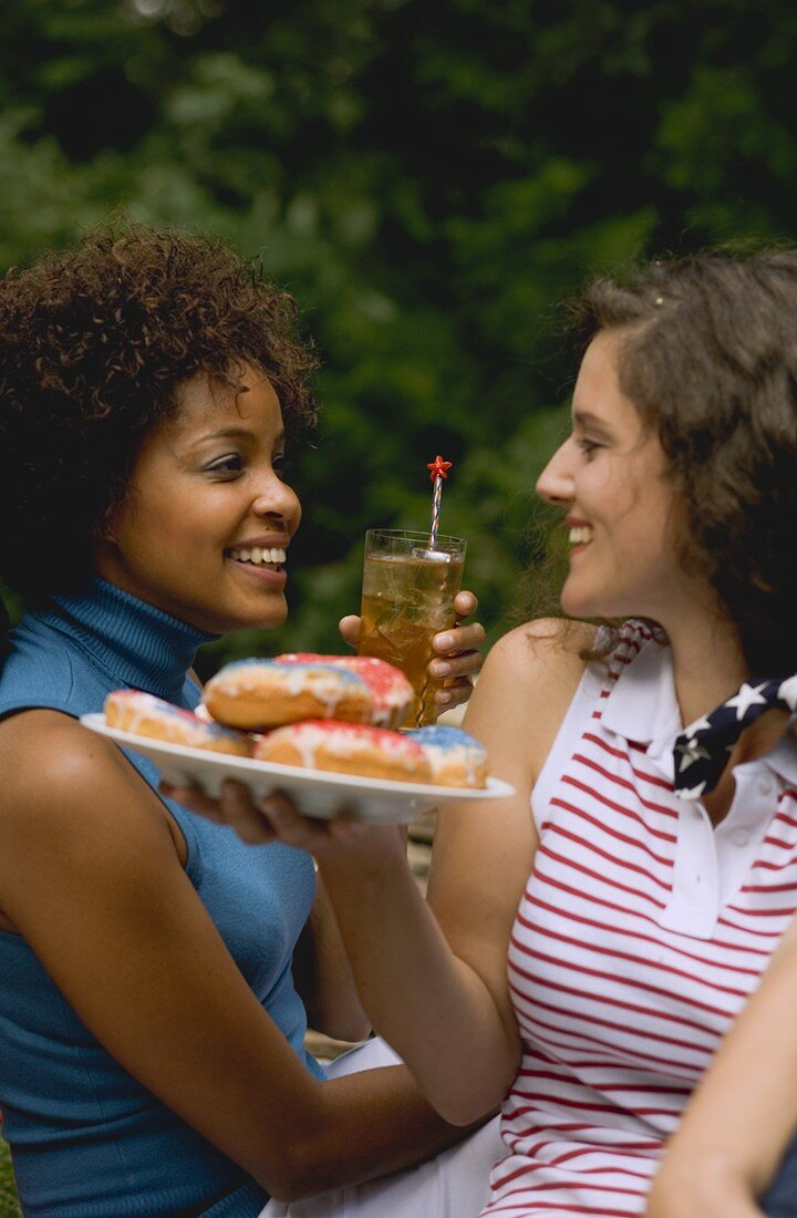 Two women with doughnuts & iced tea on the 4th of July (USA)