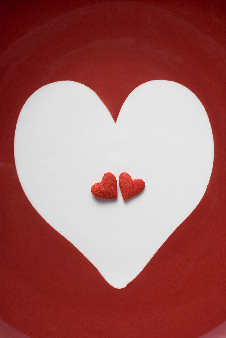 Two red sugar hearts in a white heart