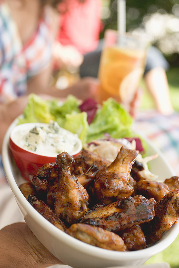 Hands holding chicken wings with salad, people in background