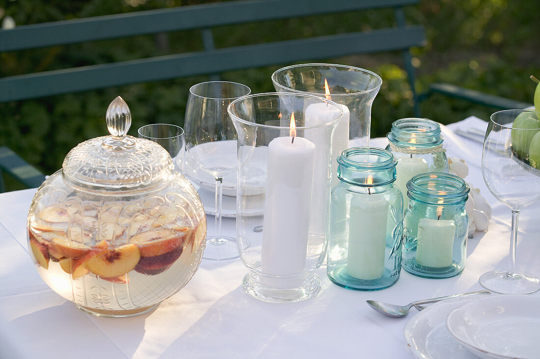 Peach punch, windlights and glasses on table in garden