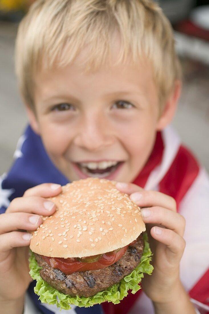 Small boy holding hamburger (4th of July, USA)