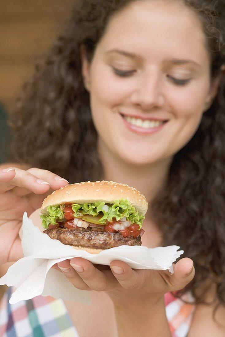 Woman holding hamburger on paper napkin