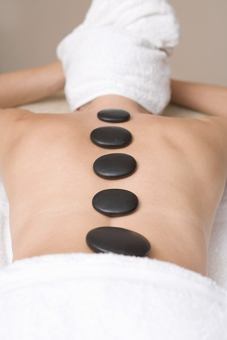 Woman having LaStone Therapy (healing therapy using stones)