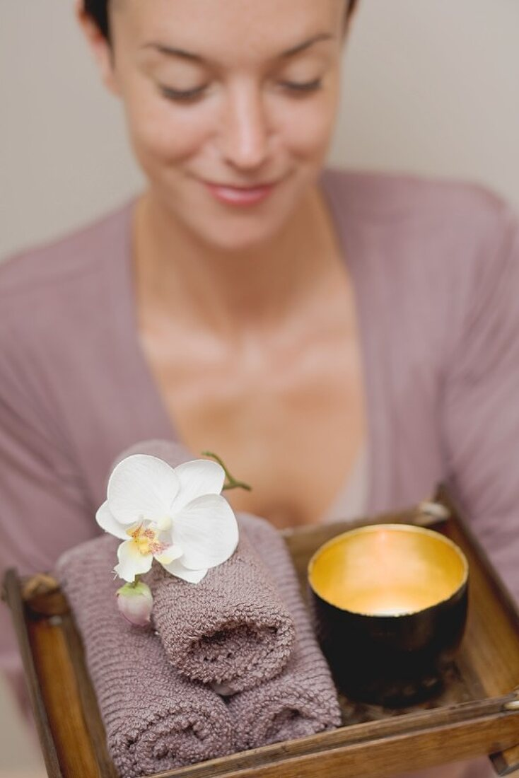 Woman holding bowl of water, orchid and towels on tray