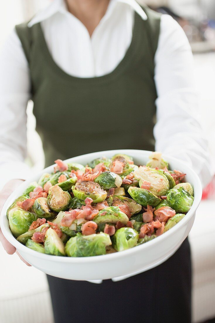 Woman holding Brussels sprouts with bacon in white dish