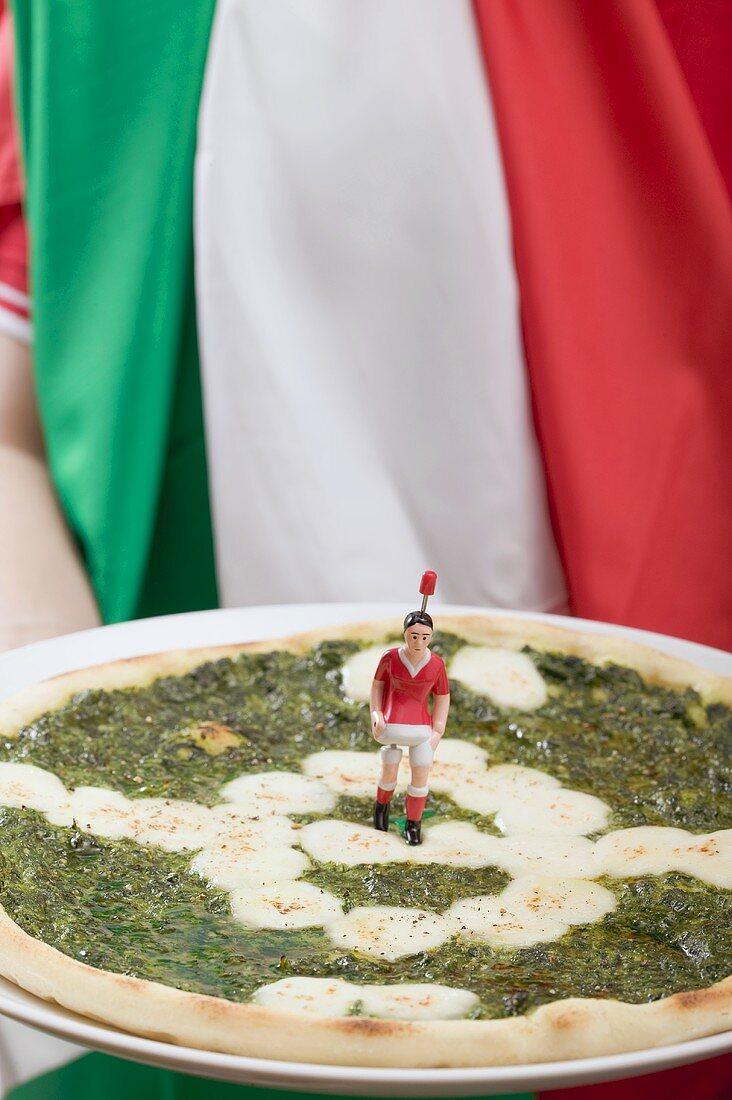 Football fan holding spinach and mozzarella pizza (Italy)