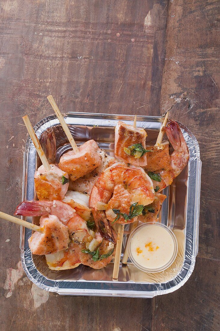 Salmon & prawn skewers with mint & sauce in aluminum dish