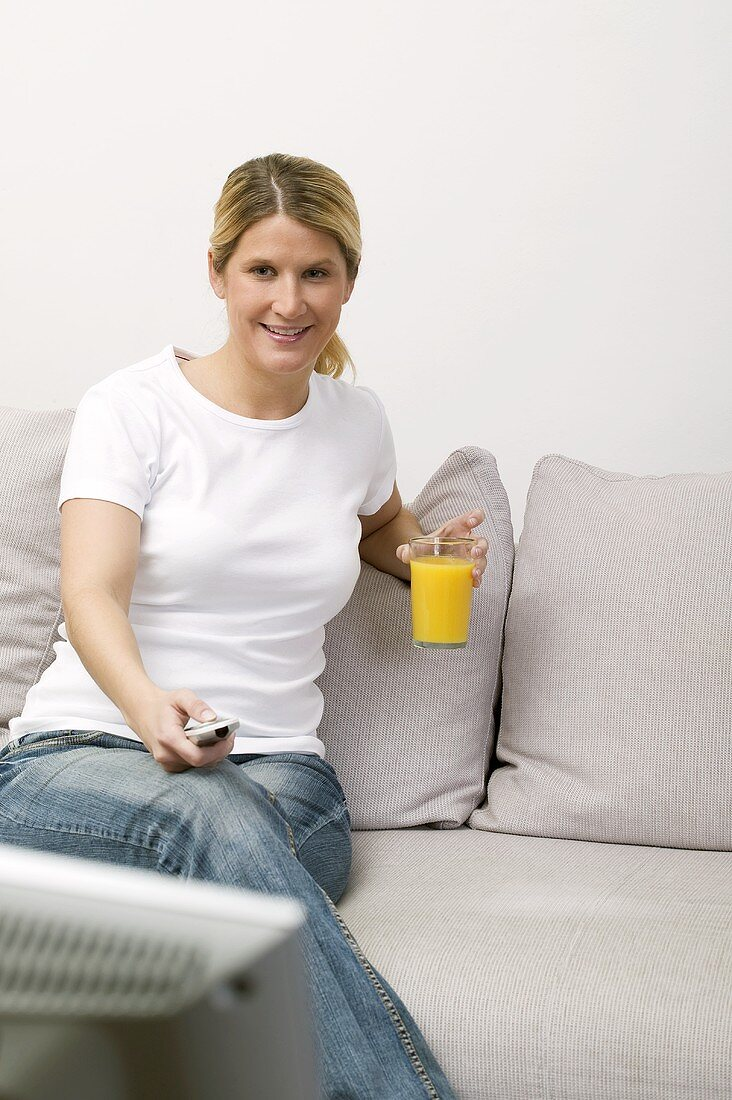 Woman with glass of orange juice watching TV
