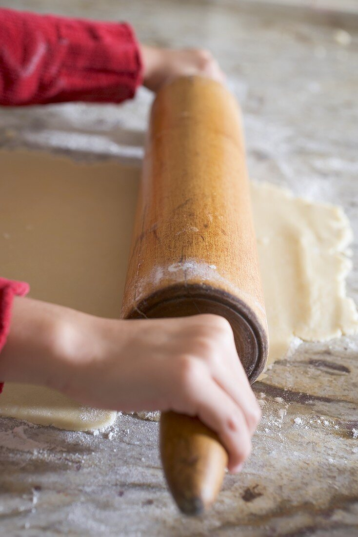 Child's hands rolling out biscuit dough