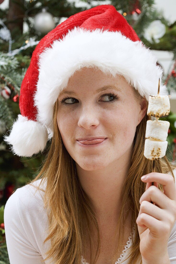 Woman in Father Christmas hat holding marshmallow skewer