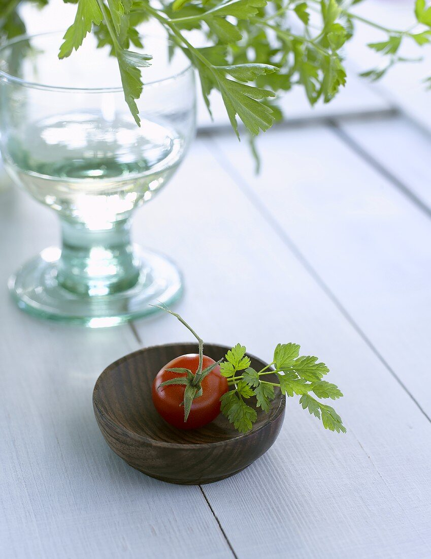 Tomato and parsley in small wooden bowl, glass of water