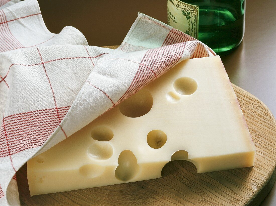 Emmental cheese with cloth on wooden board