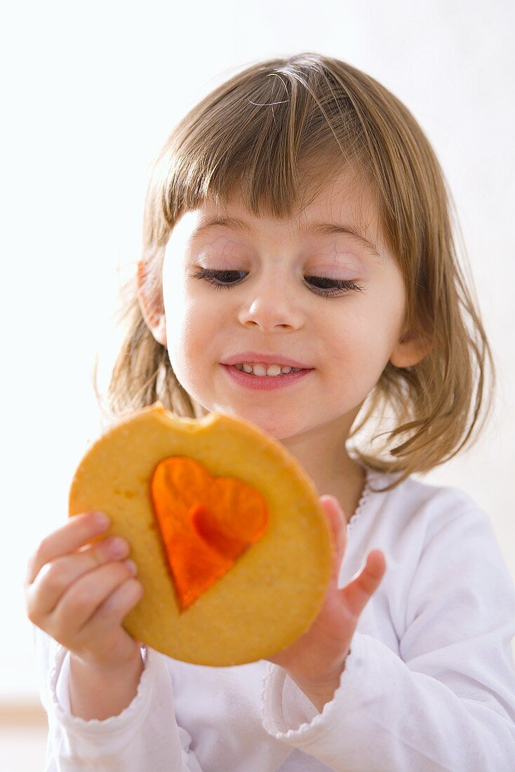 Small girl with window cookie (biscuit with sugar window)