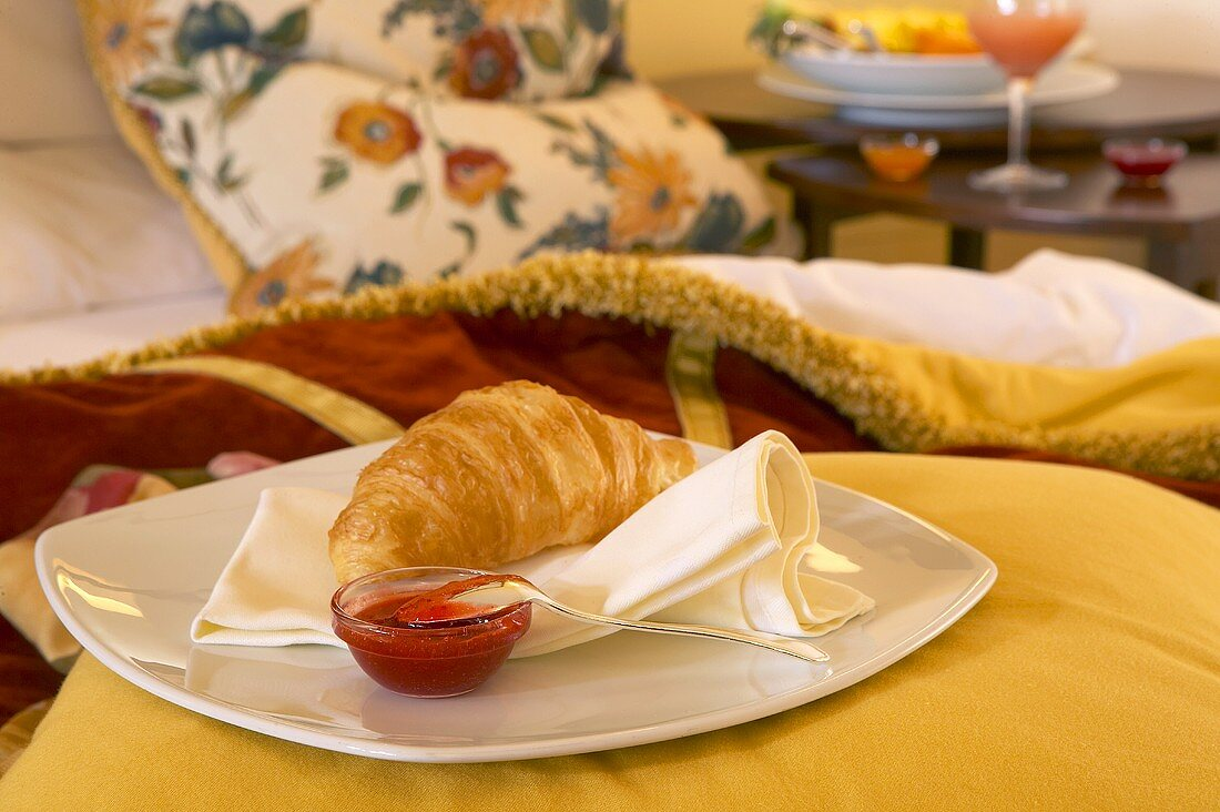 Croissant and jam on a plate on a bed