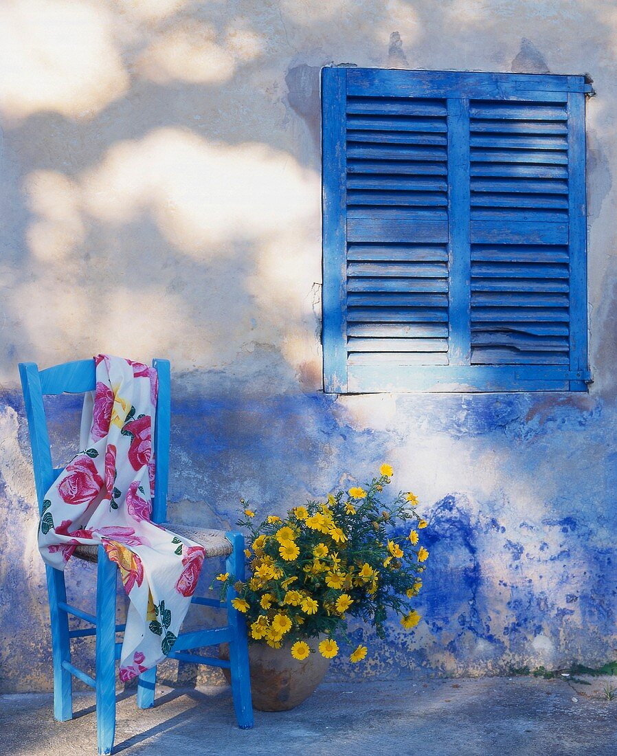 Garden chair with fabric and flowers by house wall