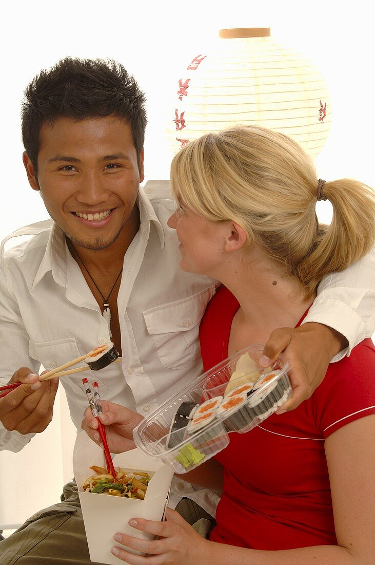 Young couple with sushi and box of noodles