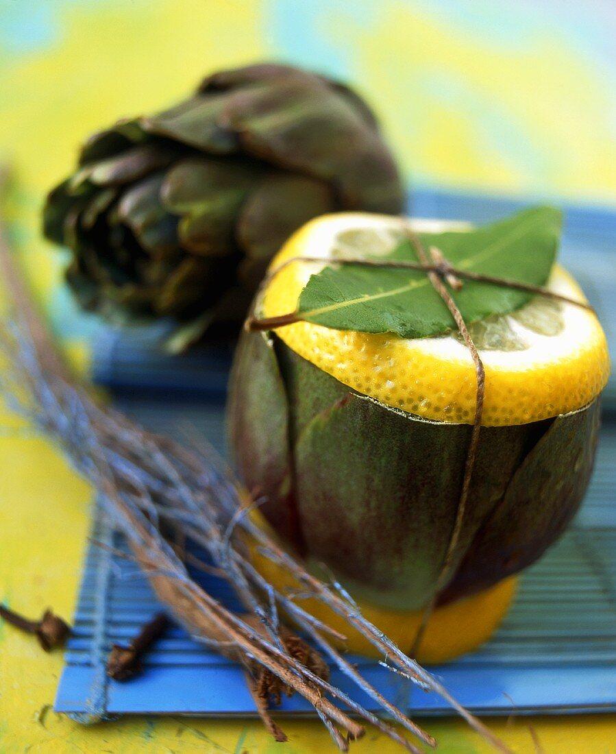 Artichoke with slice of lemon and bay leaf