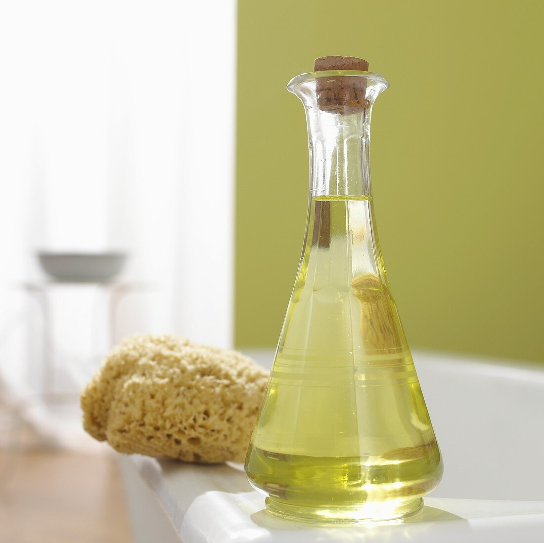 Grape seed oil and natural sponge on side of bath