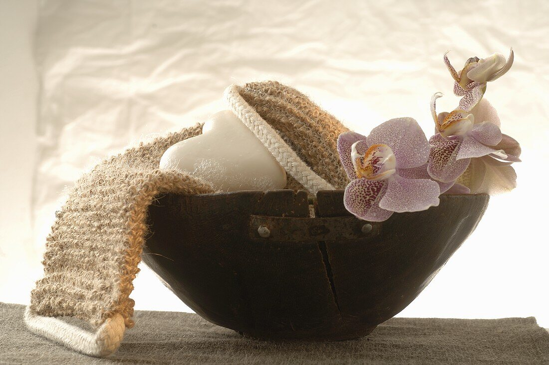 Back strap massager, heart-shaped soap, orchids in wooden bowl