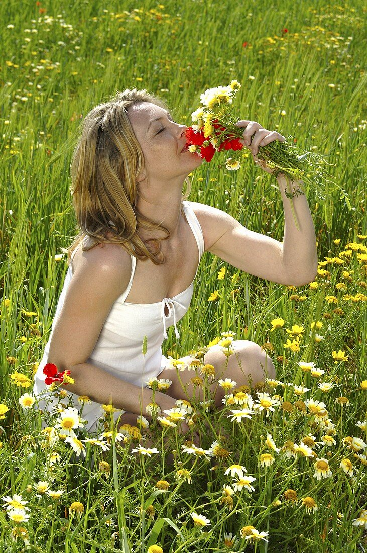 Young woman in a meadow sniffing a bunch of flowers