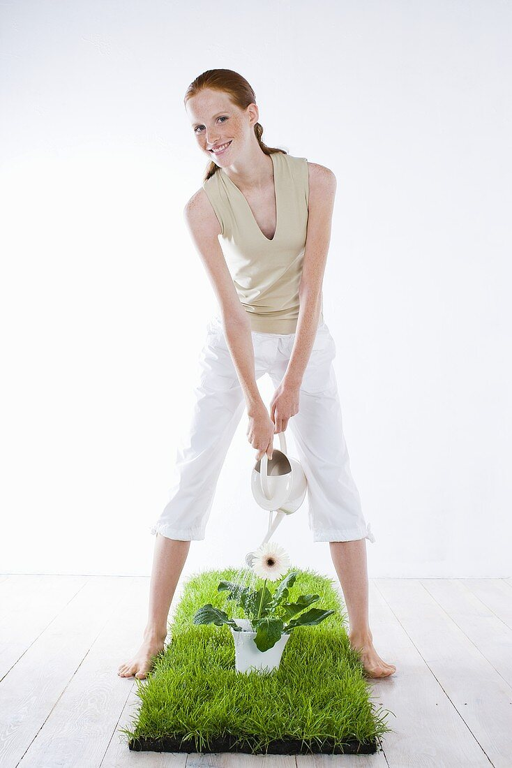 Young woman watering a plant