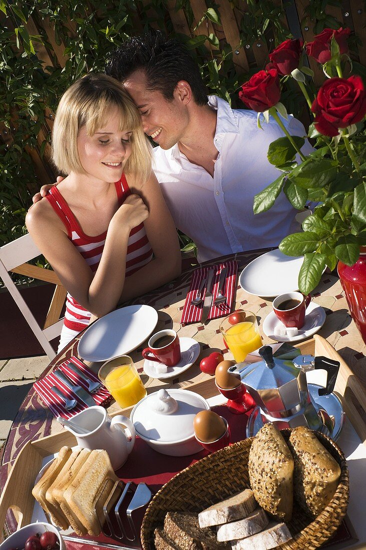 Couple sitting at breakfast table out of doors