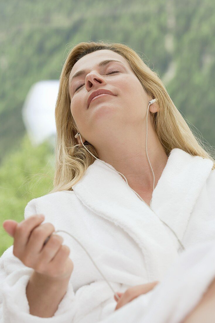 Woman in white bathrobe listening to music in garden