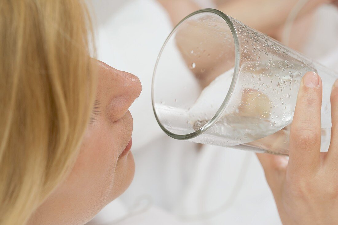 Woman drinking a glass of mineral water