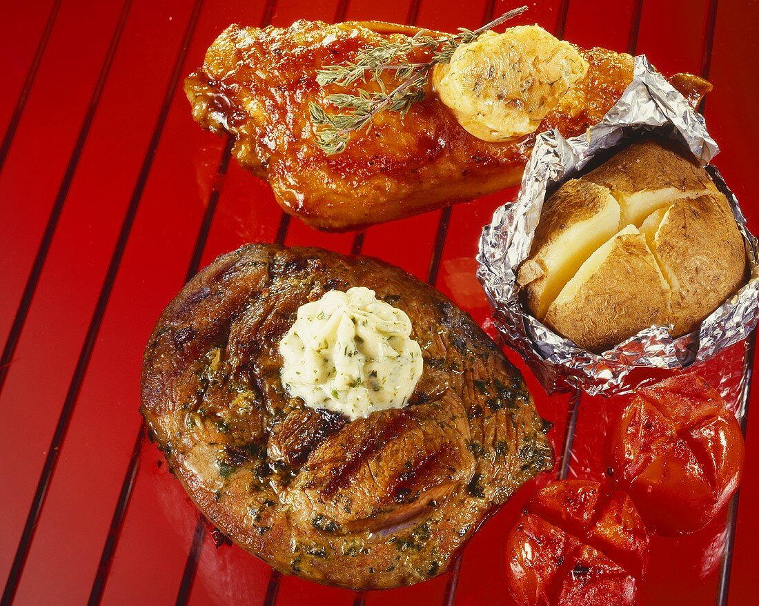 Neck steak, chicken breast, a potato and tomatoes on the barbeque