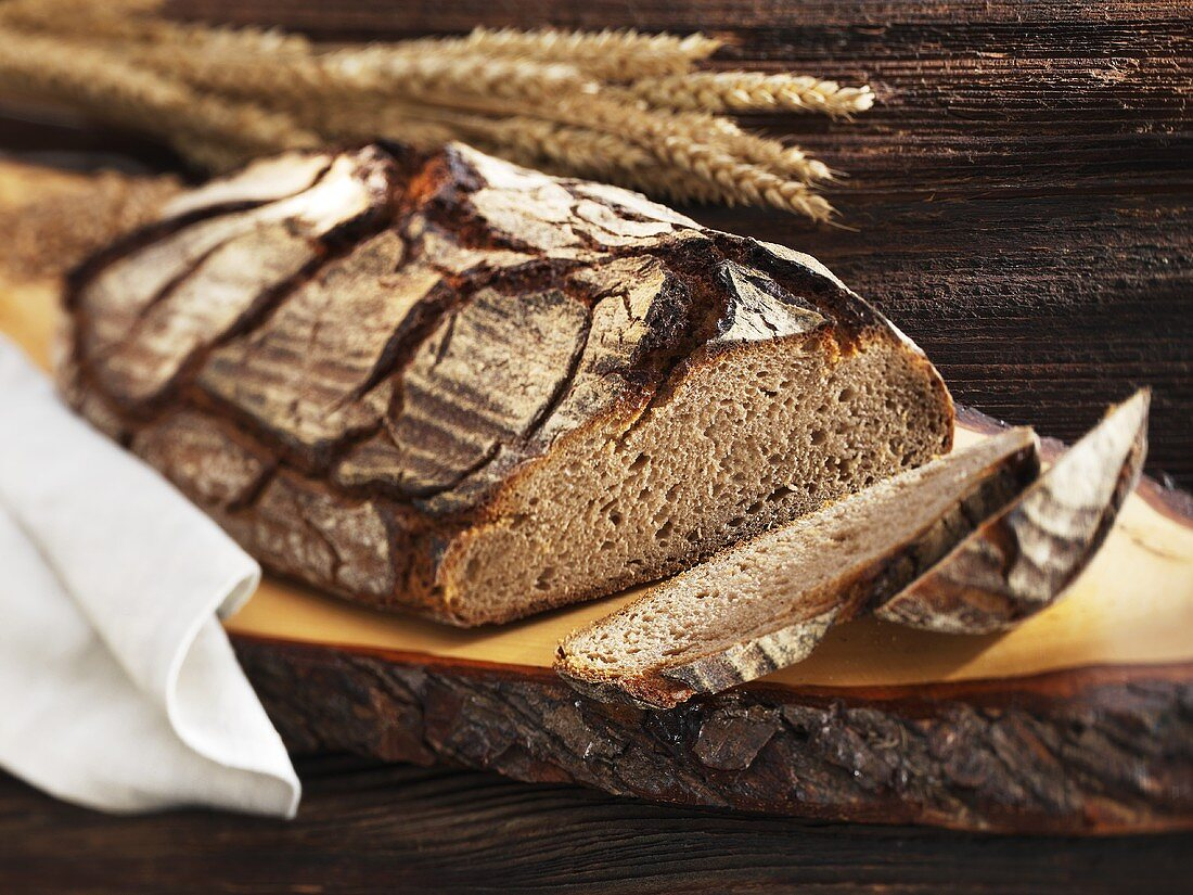 A rustic country loaf on a slice of wood