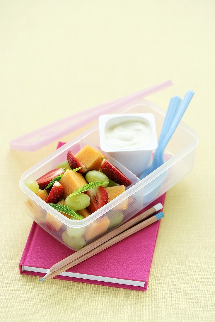 A lunchbox filled with fruit and yogurt