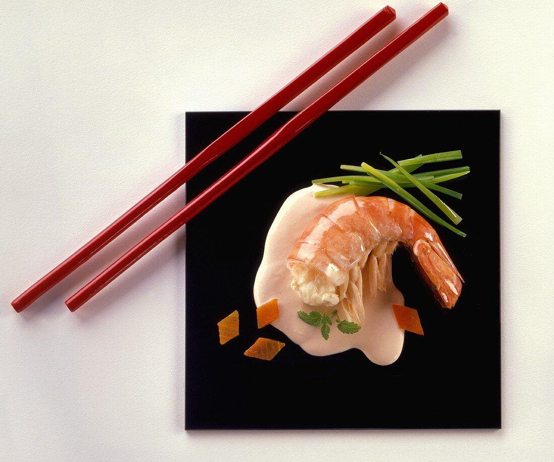 King prawn on black platter with red chopsticks