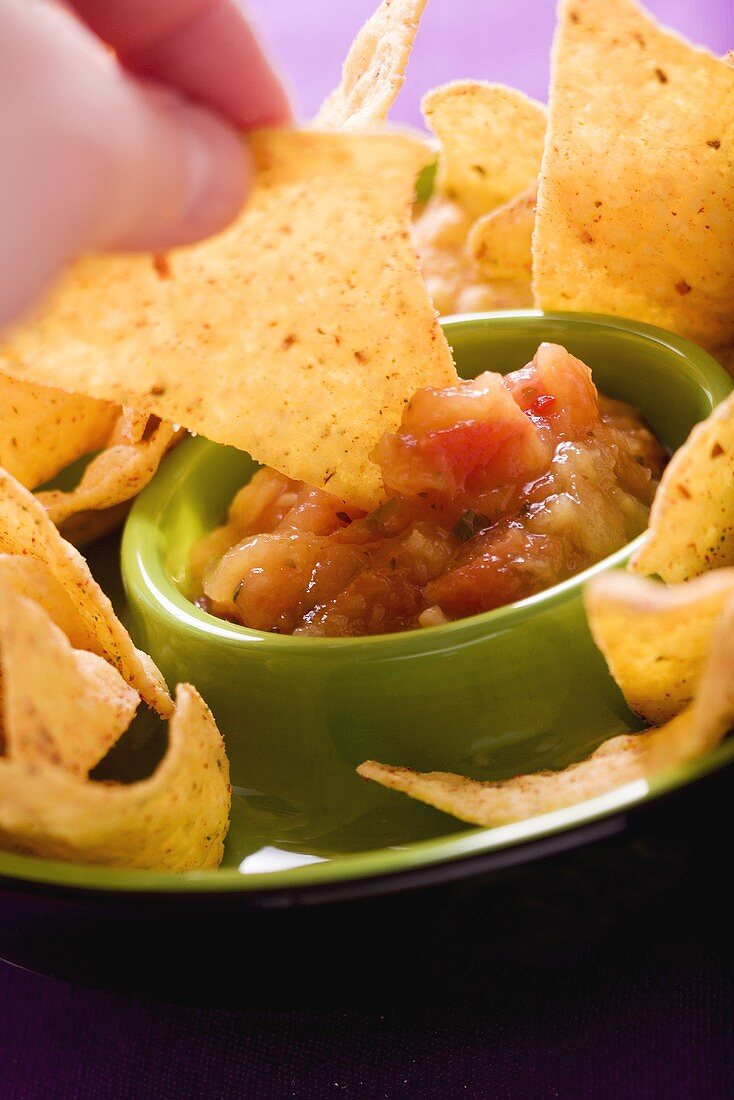 Tortilla chip being dipped in tomato salsa
