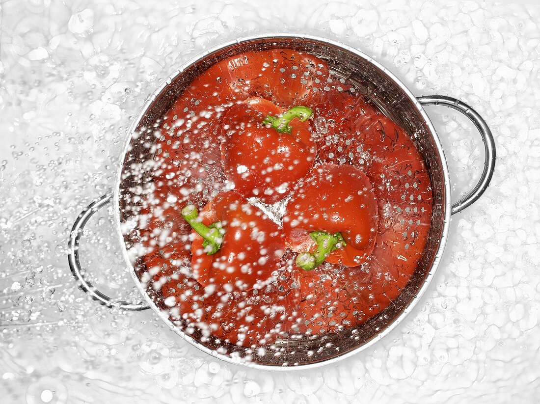 Peppers in a colander being sprayed with water