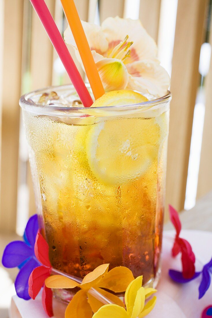 Cuba Libre with slice of lemon and amaryllis flower