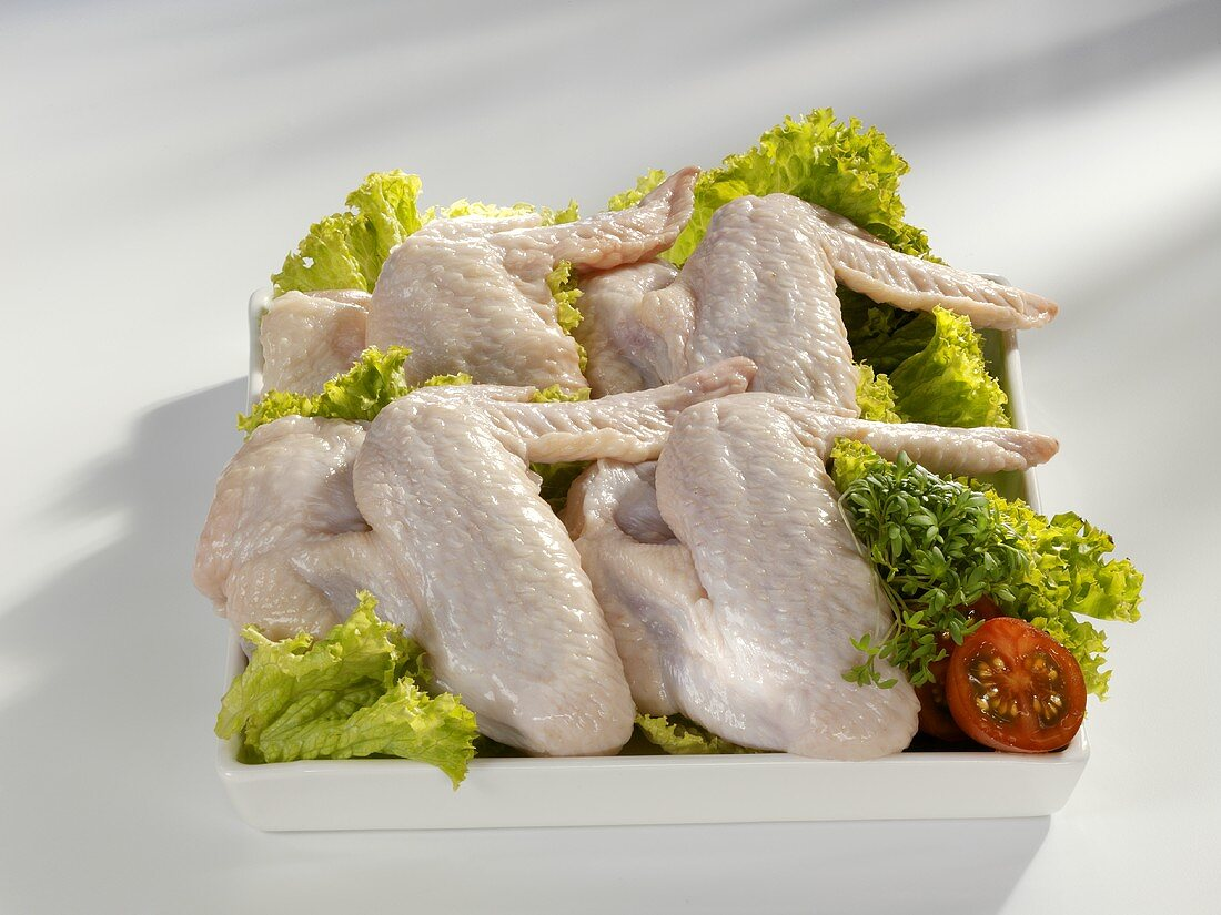 Raw chicken wings with salad garnish