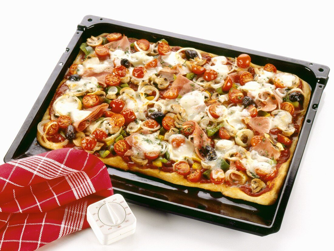 Colourful pizza topped with olives, mushrooms, ham & tomatoes