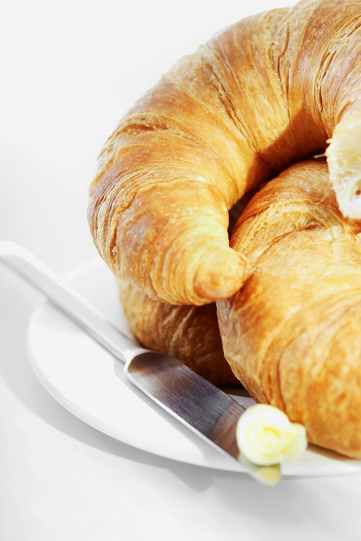 Croissants on a plate with knife and butter