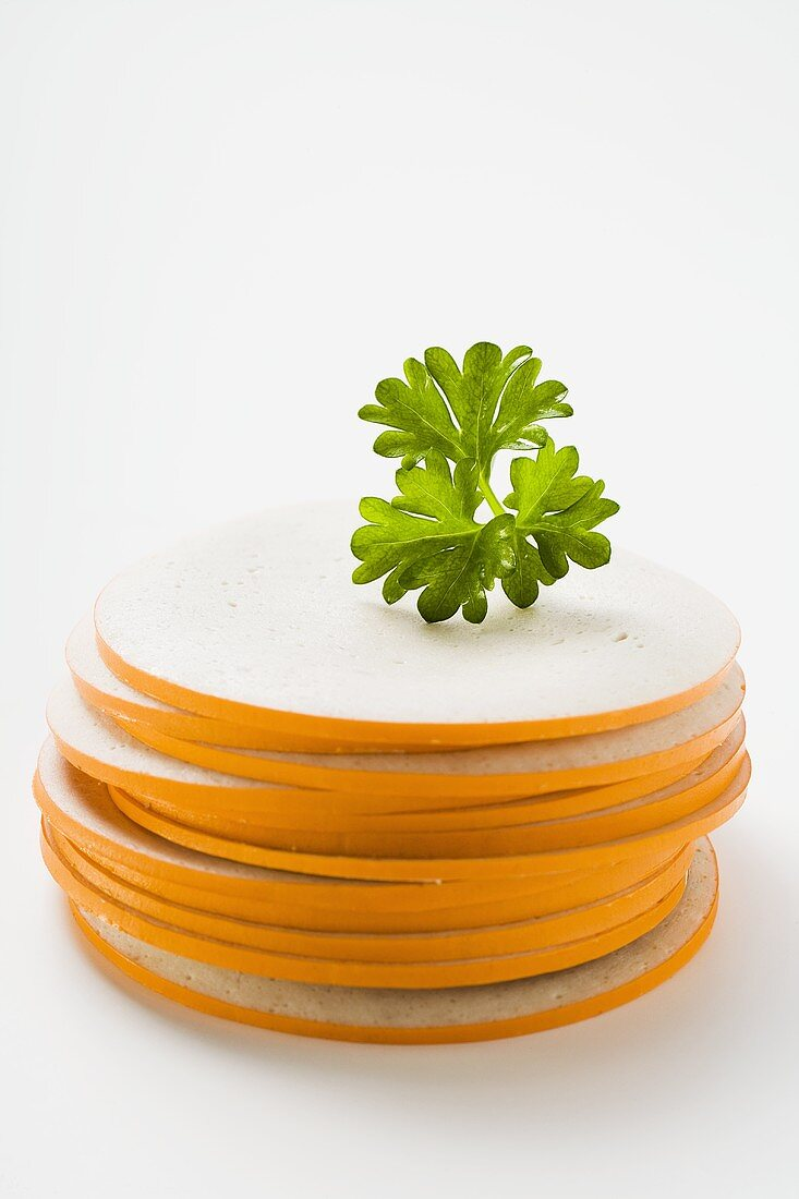 Slices of Gelbwurst (pork & veal sausage) in a pile with parsley